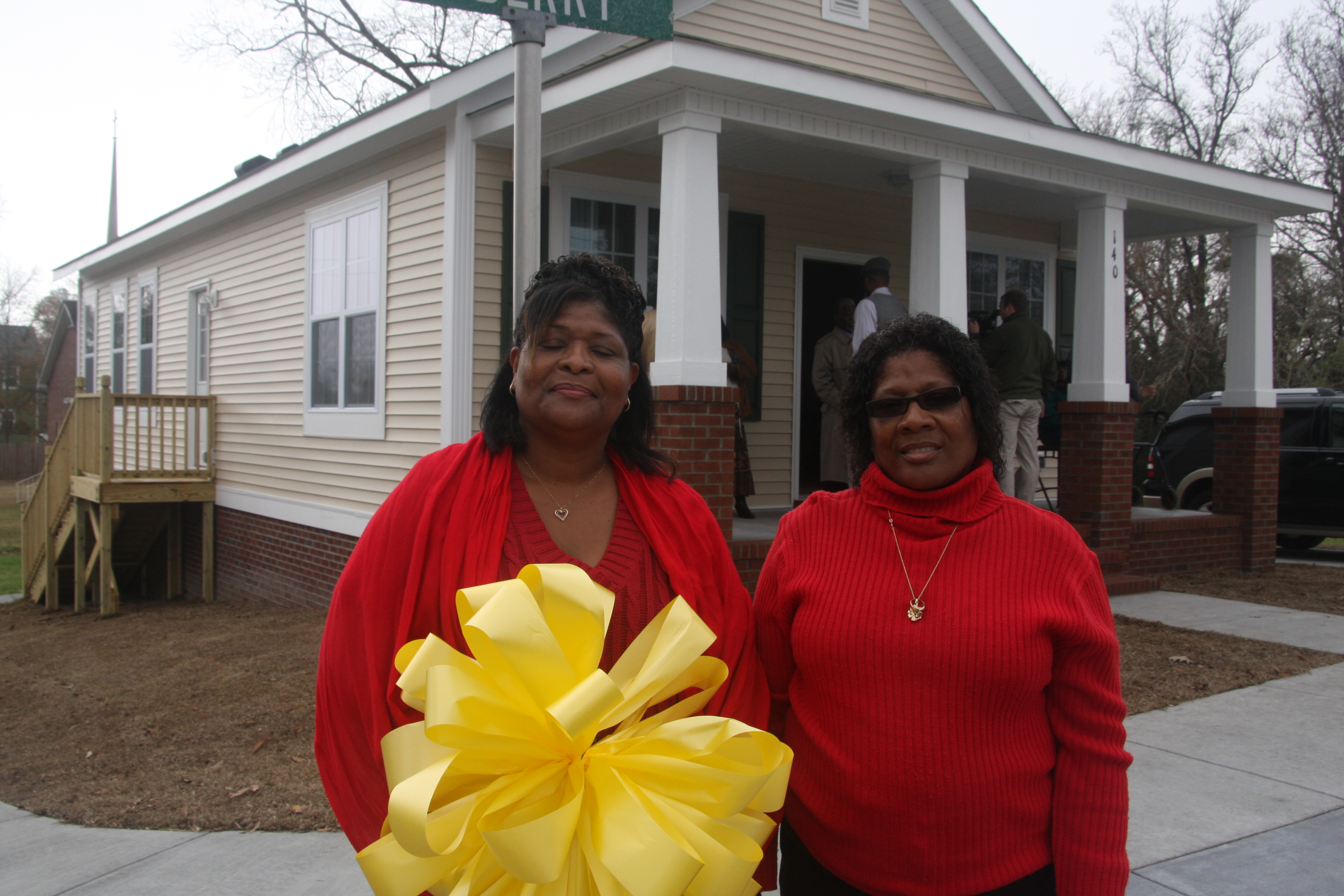 2 Women in Front of Home with Big Yellow Bow